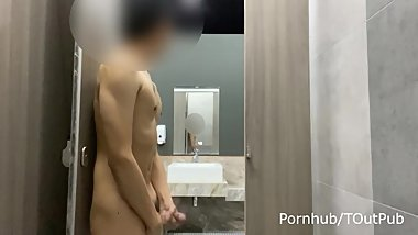 Naked in front of mirror in public toilet at gas station