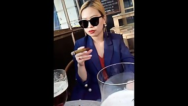 Blonde chinese business hottie enjoying her cigar g her cigar.